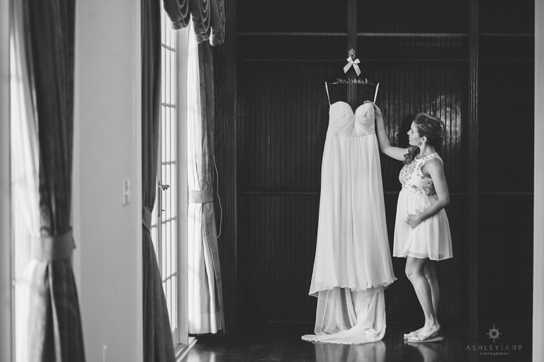 Pregnant bride looking at her wedding dress hanging up.