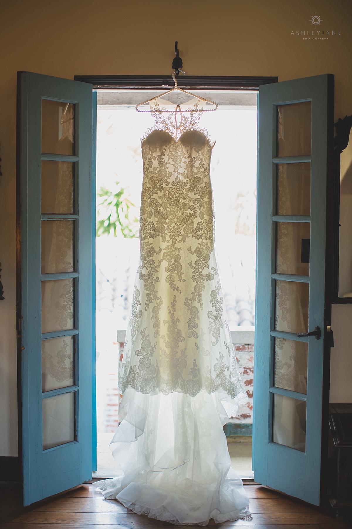 Casa Feliz | Lilac Garden Party Wedding Trumpet wedding gown hanging from blue shutter french doors