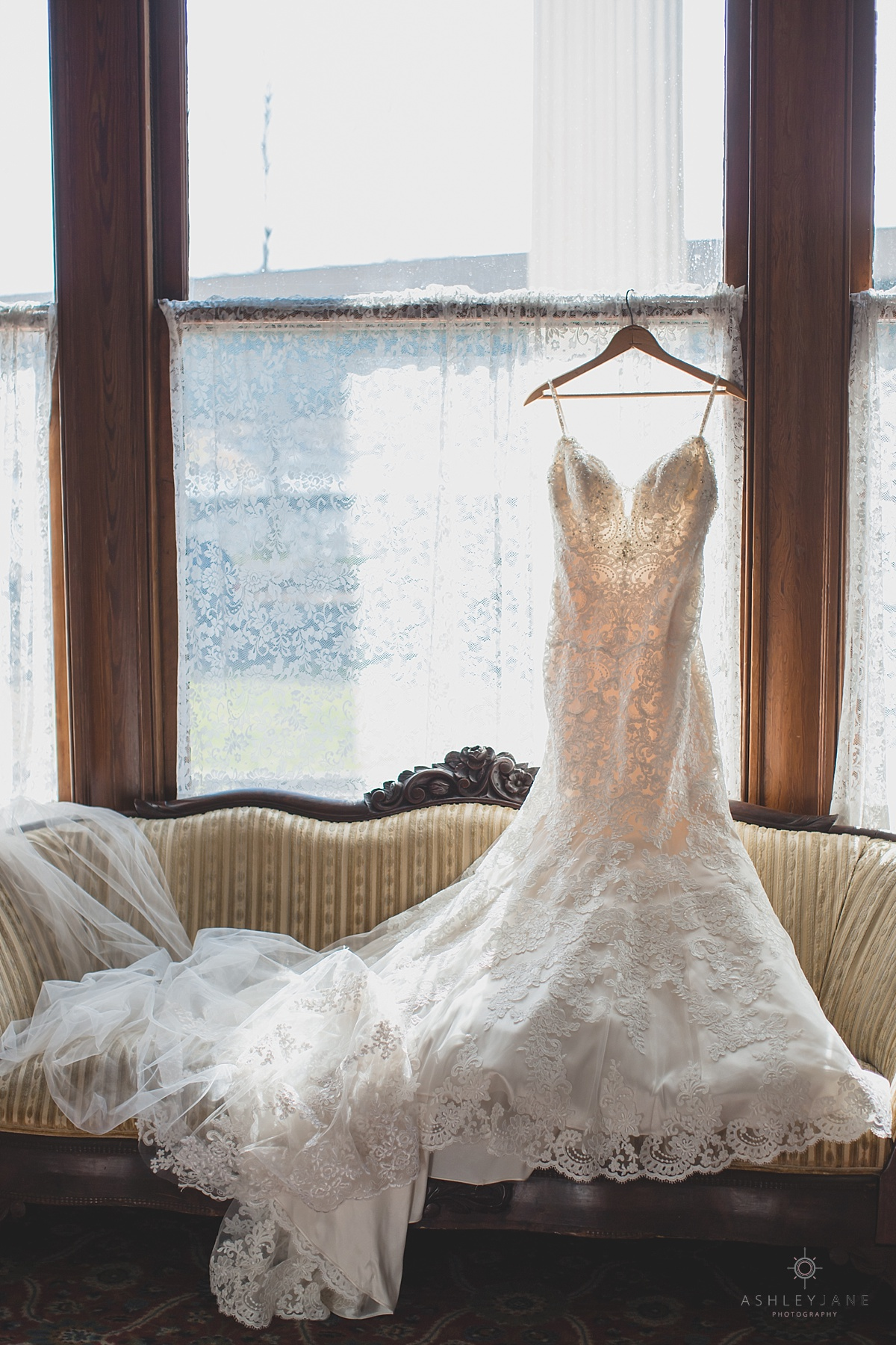 Courtyard at Lake Lucerne Lace spaghetti trumpet Mori Lee bridal gown hanging from window