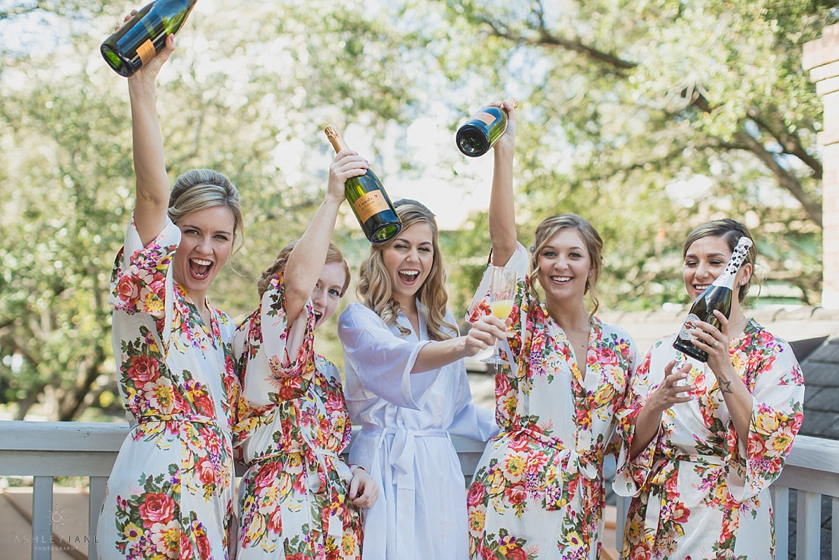 Bride and bridesmaid toasting with champagne in their robes while getting ready