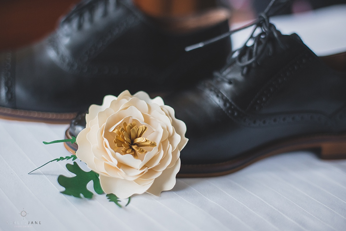 Paper flower boutonniere and black oxfords for the groom