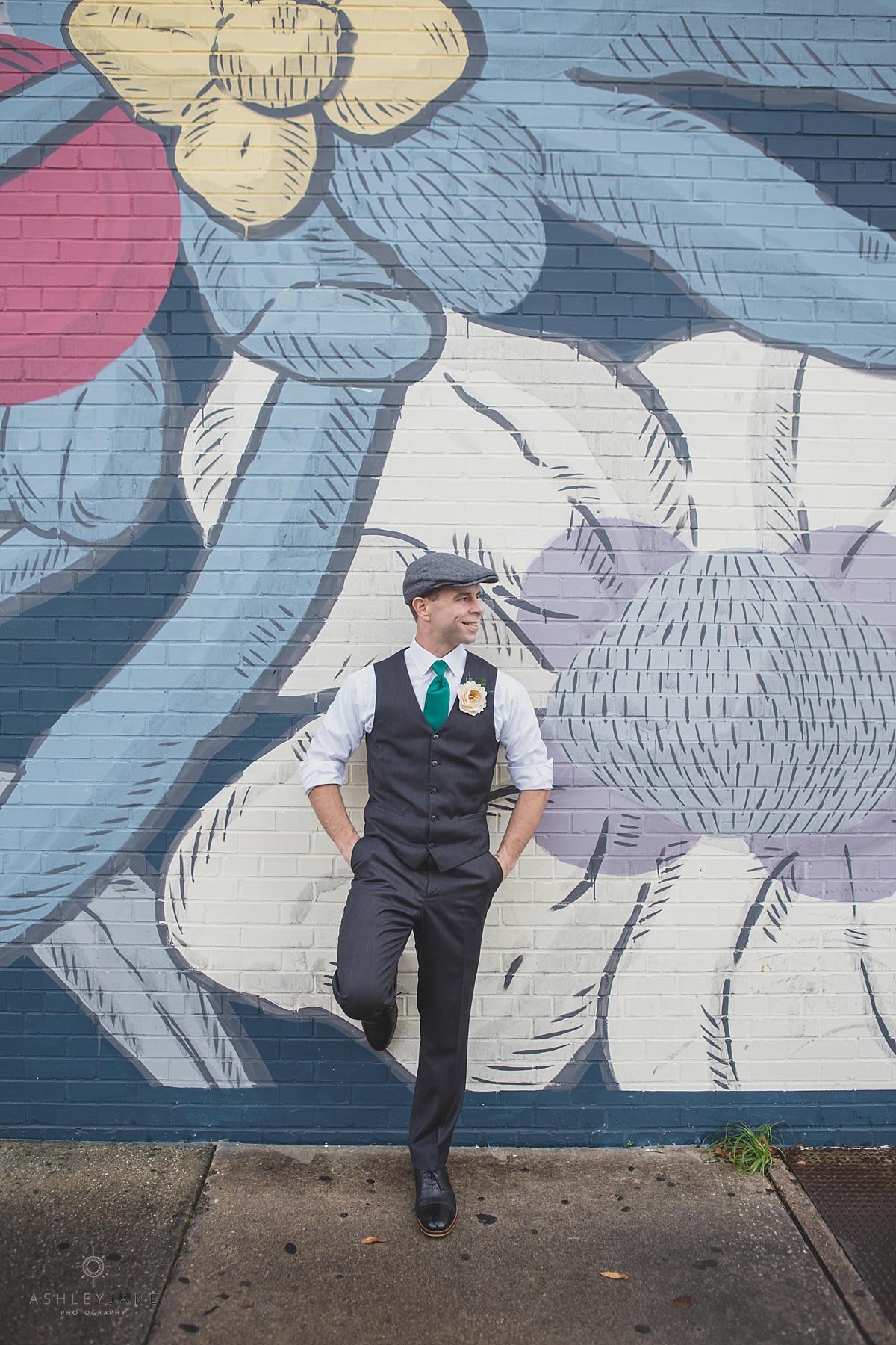 Groom in his grey vest, emerald silk tie, and paper boy cap posing behind a graffiti wall