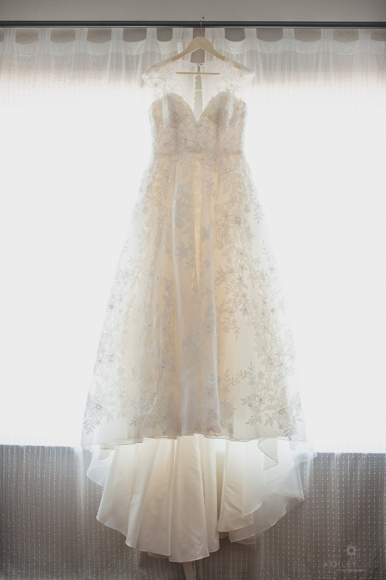Lace A line Oleg Casini Wedding Gown hanging in front of a window