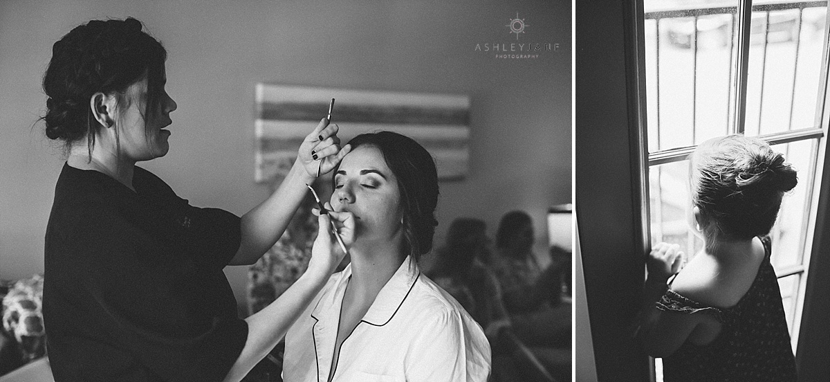 Bride getting her makeup done on her wedding day while flower girl looks out the window